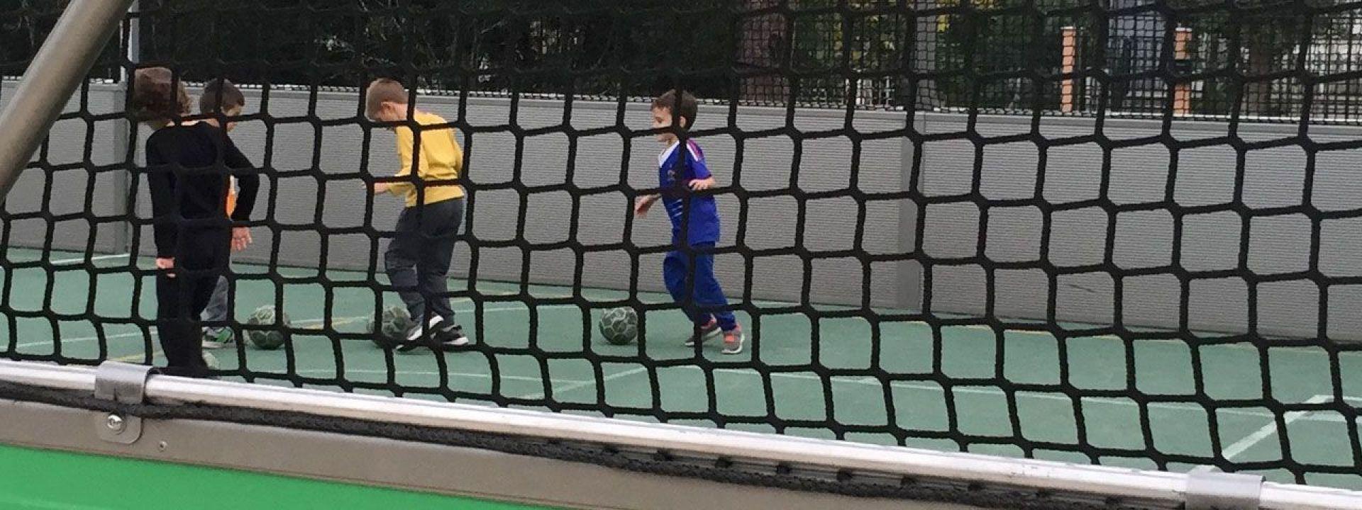 Φωτογραφία από παιδιά που παίζουν ποδόσφαιρο σε κλειστό γήπεδο στο ΚΠΙΣΝ
