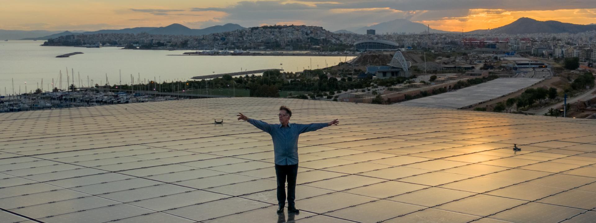 Φωτογραφία του συνθέτη Δημήτρη Καμαρωτού πάνω στο Ενεργειακό Στέγαστρο του ΚΠΙΣΝ με θέα τη θάλασσα και τη μαγευτική δύση του ηλίου