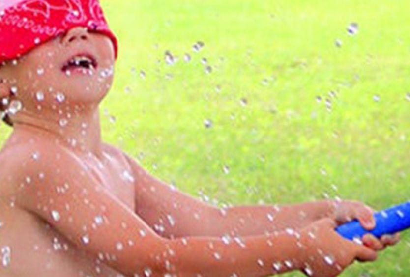 Φωτογραφία απο παιδάκι που πετάει νερό με λάστιχο
