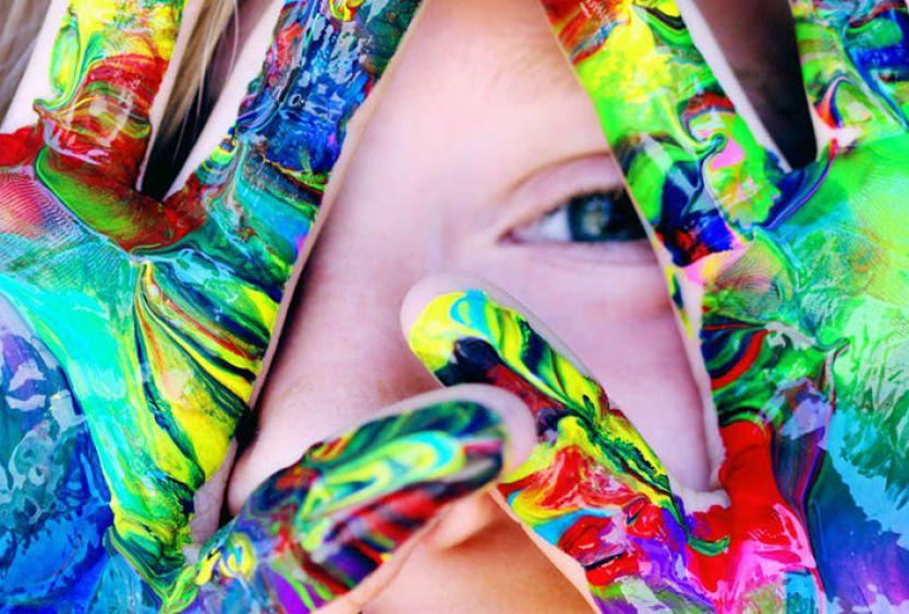 Φωτογραφία από παιδί που παίζει με χρώματα