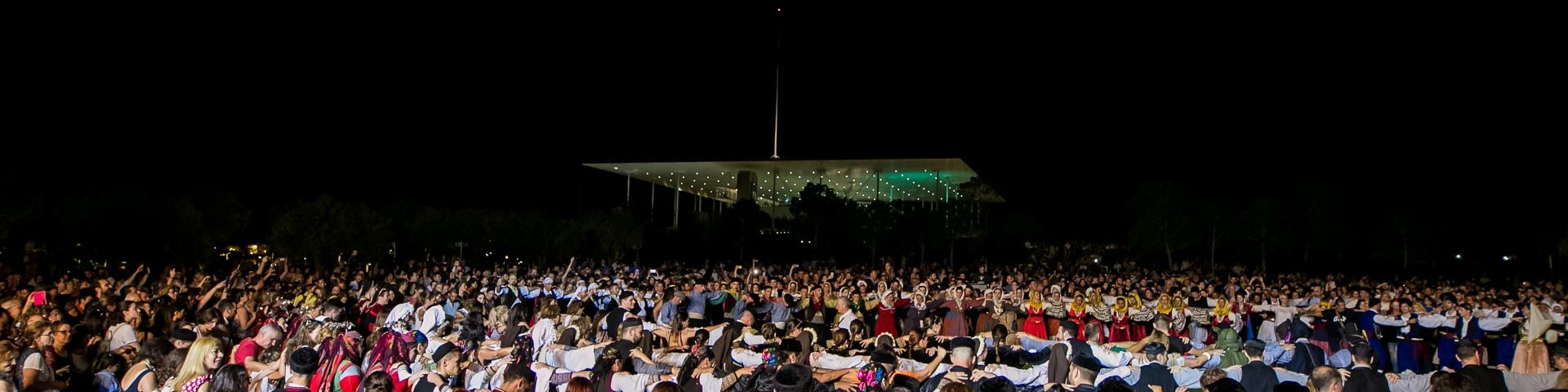 Flock of visitors at the Stavros Niarchos Park at night during an event at the SNFCC