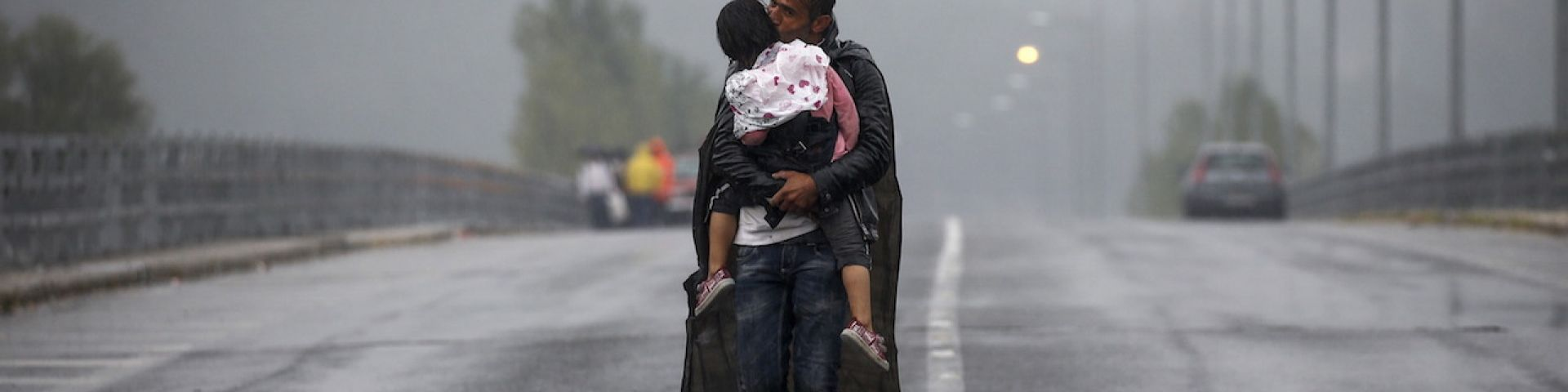 Yannis Behrakis photo of a refugee father carrying his child in the rain